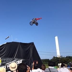 バイクが空を飛ぶ!青い空と白い煙突、そして空飛ぶライダー。
