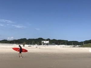 青い空と綺麗な広い砂浜、そして真っ赤なサーフボードを抱えた女性サーファー。素敵じゃない?!