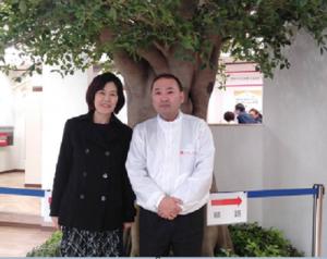 YUCACO社のシンボルツリー前で水野谷社長と…